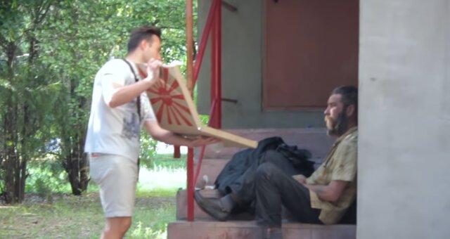 Mann gibt Pizza einem Obdachlosen. Quelle: Screenshot Youtube